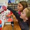 BEN MIKESELL | THE GOSHEN NEWS<br /> Third-grader Avianna Brown, right, pours vinegar into a volcano as her partner Dillyn Casey watches on during science fair judging Thursday morning at Ox Bow Elementary School.