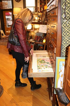 SHEILA SELMAN | THE GOSHEN NEWS<br /> Glenda Koshmider, Goshen, looks at prints at Found in downtown Goshen during Shop Small Business Saturday.