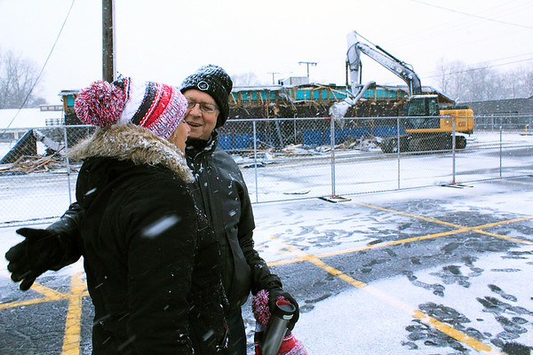 Roger Schneider | The Goshen News<br /> Denny Yoder, who once operated The Oasis bar and restaurant in Goshen with his wife Mary, greets current co-owner Heather Tobias Harren Monday morning as a backhoe operator tears down the bar building in the background.