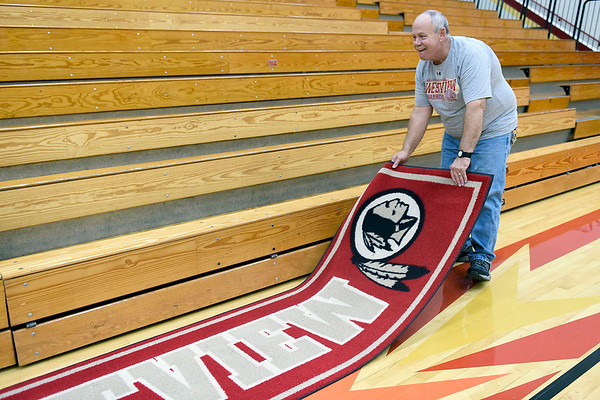 BEN MIKESELL | THE GOSHEN NEWS<br /> Custodian John Greer rolls out a mat prior to Westview's season opener Tuesday at Westview Jr.-Sr. High School.