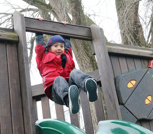 SHEILA SELMAN | THE GOSHEN NEWS<br /> Josiah Arritt, of Borneo, Malaysia, swings from the top of the slide at Tommy's Kids Castle at Shanklin Park in Goshen Friday afternoon. Arritt, his parents James and Monique (DePue) Arritt were visiting Monique's family for the holidays.
