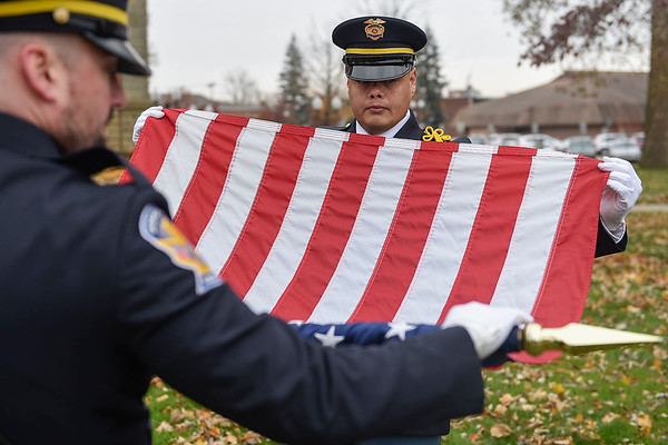 BEN MIKESELL | THE GOSHEN NEWS<br /> Goshen Police officer Alex Rosales handles the American flag after the Veterans Day ceremony Monday morning outside the Elkhart County Courthouse in Goshen.