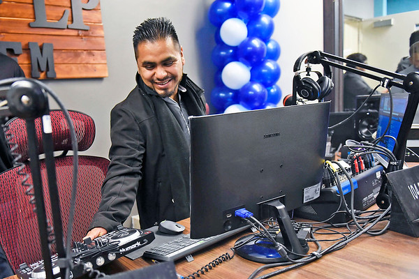 BEN MIKESELL | THE GOSHEN NEWS<br /> Production manager Roberto Venegas sets up equipment during the grand opening of Radio Horizonte's new studio Saturday, located underneath Centier Bank at the corner of Elkhart and Bashor Roads.