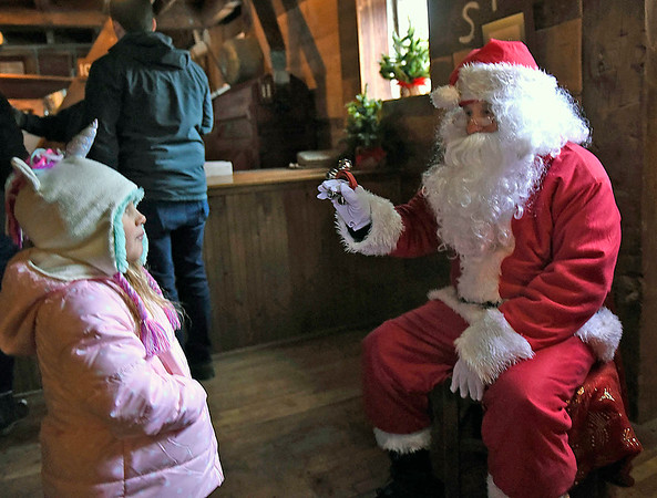 BEN MIKESELL | THE GOSHEN NEWS<br /> Tom Watson, of Goshen, greets Gabby Morley, 4, of Mishawaka, dressed as Santa Claus during the annual Holiday at the Mill event Saturday at Bonneyville Mill County Park in Bristol. Tom and his wife Pat Watson, who regularly volunteer for the Elkhart County Parks Department, dressed as Santa and Mrs. Claus for this year's event.