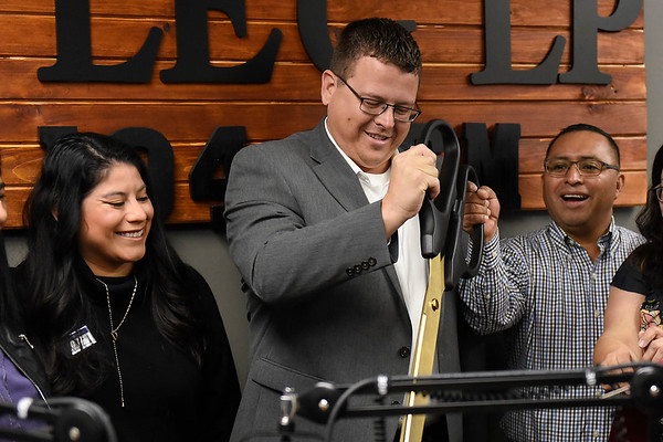 BEN MIKESELL | THE GOSHEN NEWS<br /> Nick Kieffer, Goshen Chamber of Commerce President, center, cuts the ribbon with Adriana Garcia Bontreger, left, and Manny Cortez, right, during the grand opening of Radio Horizonte's new studio Saturday, located underneath Centier Bank at the corner of Elkhart and Bashor Roads.