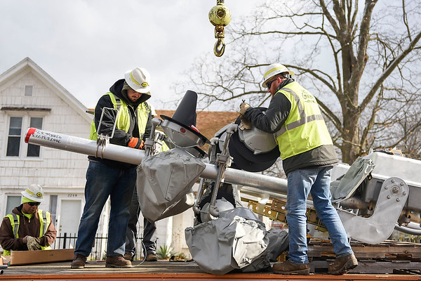 BEN MIKESELL   THE GOSHEN NEWS<br /> Norfolk Southern workers Garrett Hall, left, and Craig Terry, right, prepare a railroad crossing light for installation Tuesday afternoon at the intersection of 9th Street and Jefferson St in Goshen. Ninth Street is in the process of being converted into a one-way street going south.