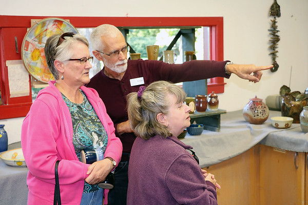 JOHN KLINE | THE GOSHEN NEWS<br /> Goshen artist Bob Smoker points out a ceramics display at the Goshen Clay Artists Guild for visitors, from left, Carol Scribner, of Goshen, and Marikae Brown, of South Bend, during the 2018 Michiana Pottery Tour Saturday afternoon.