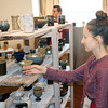 JOHN KLINE | THE GOSHEN NEWS<br /> Sarah Richcreek, of Indianapolis, reaches in to get a closer look at a ceramic cup while visiting Goshen Youth Arts during the 2018 Michiana Pottery Tour Saturday afternoon.