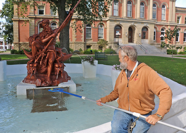 Roger Schneider | The Goshen News<br /> Rex Lechlitner, a buildings and grounds employee with Elkhart County, removes leaves Thursday from the Neptune fountain in front of the county courthouse in Goshen. Lechlitner said he spends time every day cleaning the historic fountain.