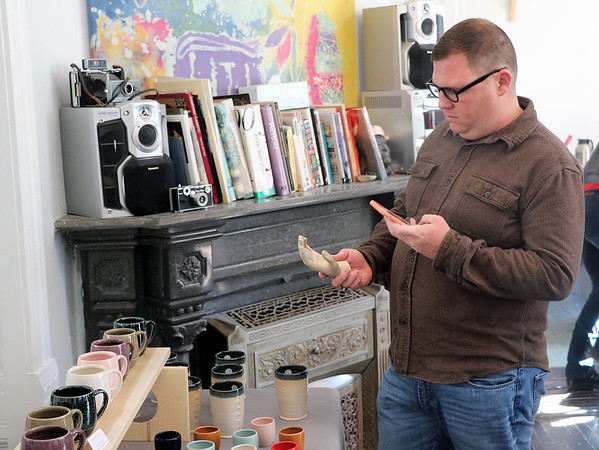 JOHN KLINE | THE GOSHEN NEWS<br /> Baxter Orr, of Goshen, snaps a photo of a piece of artwork with his cellphone while visiting Goshen Youth Arts during the 2018 Michiana Pottery Tour Saturday afternoon.