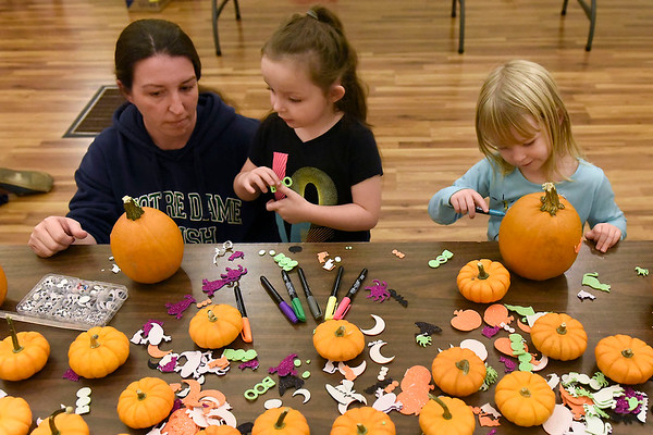 BEN MIKESELL   THE GOSHEN NEWS<br /> Misty Trenshaw, of Goshen, left, helps her daughter Jaylyn, 5, center, decorate pumpkins Friday with her cousin Nora Neff, 3, of New Paris during the First Friday festivites at the Goshen Theater. The Growing Kids Learning Center in Goshen sponsored the event, bringing in pumpkins donated from Walmart for children to decorate.