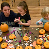 BEN MIKESELL | THE GOSHEN NEWS<br /> Misty Trenshaw, of Goshen, left, helps her daughter Jaylyn, 5, center, decorate pumpkins Friday with her cousin Nora Neff, 3, of New Paris during the First Friday festivites at the Goshen Theater. The Growing Kids Learning Center in Goshen sponsored the event, bringing in pumpkins donated from Walmart for children to decorate.