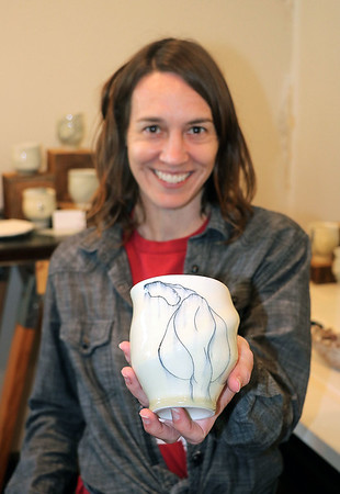 JOHN KLINE | THE GOSHEN NEWS<br /> Artist Amy Smith, of Lincoln, Nebraska, holds up one of her ceramic creations while at Goshen Youth Arts in downtown Goshen Saturday afternoon. Goshen Youth Arts, where Smith had a number of her ceramic works on display for visitors to enjoy and purchase, was one of six studios featured during the 2018 Michiana Pottery Tour.