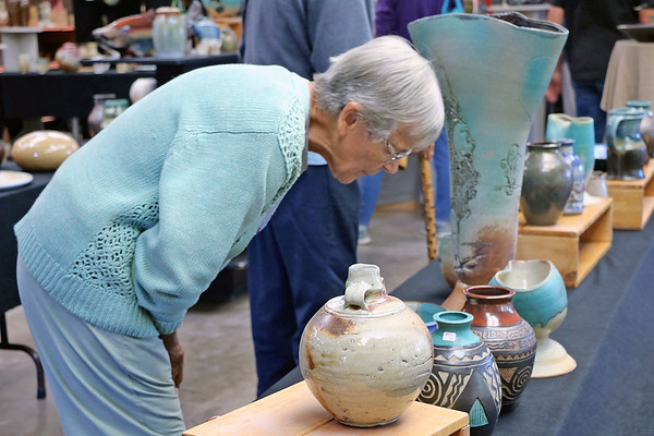 JOHN KLINE | THE GOSHEN NEWS<br /> Leah Schwartz, of Middlebury, leans in to get a closer look at one of the many ceramic works on display at the Goshen Clay Artists Guild during the 2018 Michiana Pottery Tour Saturday afternoon.