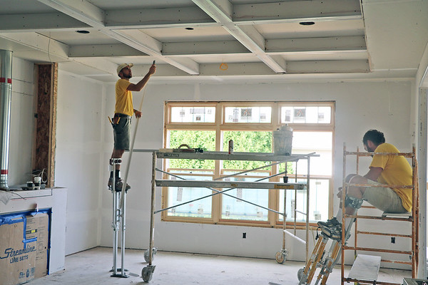 AIMEE AMBROSE | THE GOSHEN NEWS <br /> Mark Stutzman and Dave Stutzman do drywalling work with CCS Drywall Inc. at a house under construction in the Westoria subdivision in Goshen.