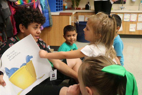 "AIMEE AMBROSE | THE GOSHEN NEWS <br /> Luis Tuchan, a freshman at Concord High School, reads ""White Rabbit's Color Book"" to kindergarten students in Mrs. Stover's class at South Side Elementary School Friday as part of South Side's annual Read, Write, Move fundraiser."