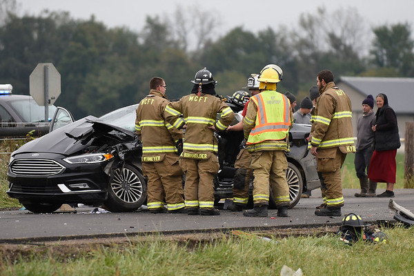 BEN MIKESELL | THE GOSHEN NEWS<br /> Millersburg-Clinton firefighters investigate a car involved in a wreck that occured Friday afternoon at the intersection of C.R. 40 and C.R. 43 near Millersburg.