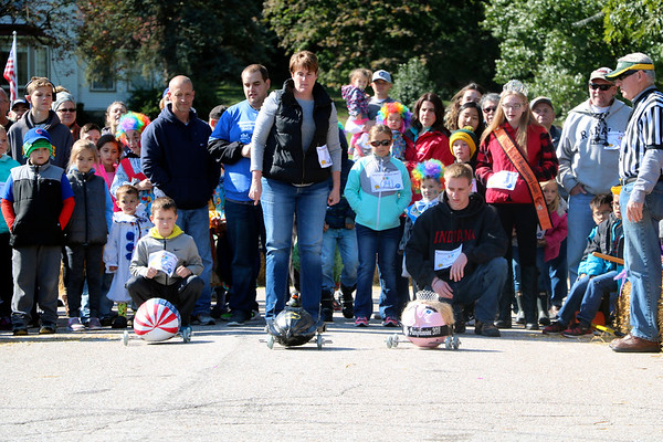 AIMEE AMBROSE | THE GOSHEN NEWS <br /> Pumpkins decorated like the Batmobile, the American flag and a pageant contestant race down West Warren Street during the first round of Middlebury's second annual Pumpkin Race on Saturday.