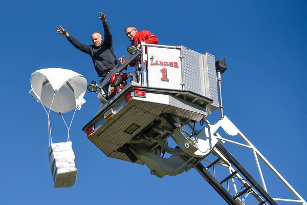 BEN MIKESELL | THE GOSHEN NEWS<br /> Goshen Fire battalion chief Steffen Schrock, left, and Goshen High School assistant principal Jim Pickard toss a pumpkin from 50 feet in the air during the annual pumpkin drop Thursday at Goshen High School.