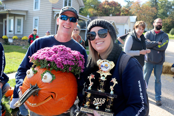 AIMEE AMBROSE | THE GOSHEN NEWS  (from left) Mark Nichols and Stacey Irelan of Elkhart Plastics hold their pumpkin and trophy after winning the corporate race during the second annual Pumpkin Race in Middlebury on Saturday.