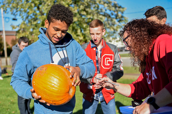 BEN MIKESELL | THE GOSHEN NEWS<br /> Goshen High School junior Dylan Steury has his pumpkin examined after it fell from a 87-foot drop Thursday morning at Goshen High School. His group cushioned the impact with foam and bungie cords, which successfully protected the pumpkin for the 50- and 87-foot drops.