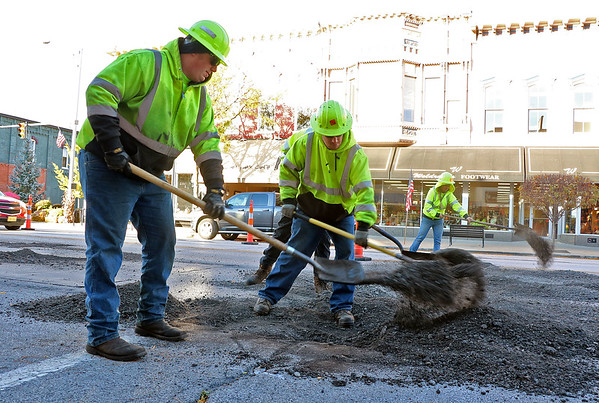 Roger Schneider | The Goshen News<br /> Gary Conn of Elkhart, left, and his fellow workers from the Elkhart location of the Indiana Department of Transportation, shovel the milled surface of Goshen's Main Street Wednesday morning. INDOT is spending time in downtown this week repairing the cracks in the road surface.