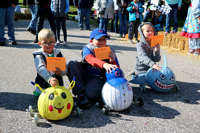AIMEE AMBROSE   THE GOSHEN NEWS  Drew Pontius, 8, Logan Scholten, 4, and Braxton Lantzer, 5, pose as the first, second and third place winners, respectively, of the second annual Pumpkin Race in Middlebury on Saturday. Pontius raced a Chicago Cubs pumpkin, Scholten's pumpkin was decorated like Pikachu from Pokemon. Lantzer had a shark pumpkin.