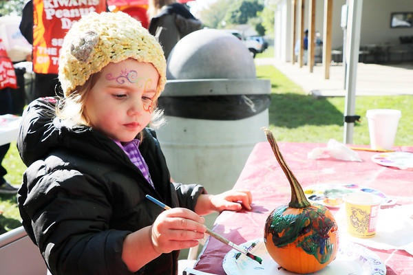 AIMEE AMBROSE | THE GOSHEN NEWS <br /> Vega Richardson, Elkhart, paints a small pumpkin at a table during the Syracuse Fall Harvest Festival at Lakeside Park on Saturday.