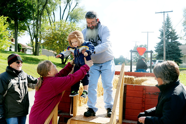 AIMEE AMBROSE | THE GOSHEN NEWS <br /> (from top) Richard Penrod, Goshen, hands his grandson, Hunter Green of California, down to his wife, after the family went on a hay ride during the Syracuse Fall Harvest Festival at Lakeside Park on Saturday.