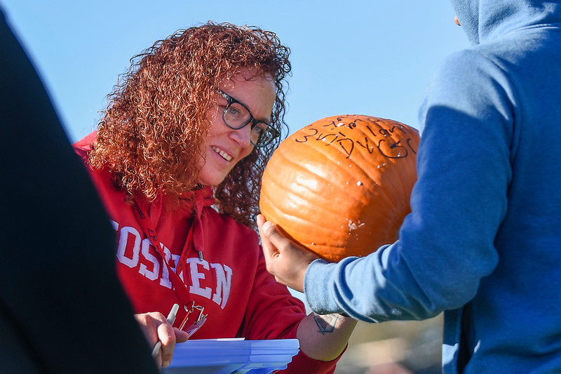 BEN MIKESELL | THE GOSHEN NEWS Goshen High School engineering teacher Jen Yoder inspects junior Dylan Steury's pumpkin to see if it survived falling from 50 feet during the annual pumpkin drop Thursday morning at Goshen High School.