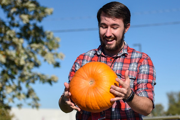 BEN MIKESELL | THE GOSHEN NEWS<br /> Goshen High School senior Carter Self examines his group's pumpkin after it fell from a 87-foot drop Thursday morning at Goshen High School.