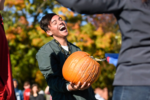 "BEN MIKESELL | THE GOSHEN NEWS<br /> Goshen High School senior Javier Castillo laughs with classmates after their pumpkin fell from a 50-foot drop and broke open Thursday morning at Goshen High School. Students in Jen Yoder's engineering classes began designing for the annual pumpkin drop at the beginning of October, but had only one class period to construct their designs. ""If we had a parachute on ours it probably would have survived,"" Castillo said."