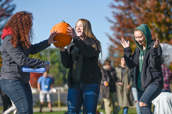 BEN MIKESELL | THE GOSHEN NEWS<br /> Goshen High School sophomore Maddie Swallow, center, and junior classmate Becca VanDiepenbos, right, celebrate with their pumpkin after it survived a 50-foot drop Thursday morning at Goshen High School.