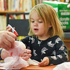 BEN MIKESELL | THE GOSHEN NEWS<br /> Chloe Brubaker, 2, of Dunlap, draws eyes on her plastic bag ghost during the weekly kids craft session Monday at Better World Books in Goshen. Throughout the month, Better World Books is hosting free Halloween-themed craft sessions every Monday for children.