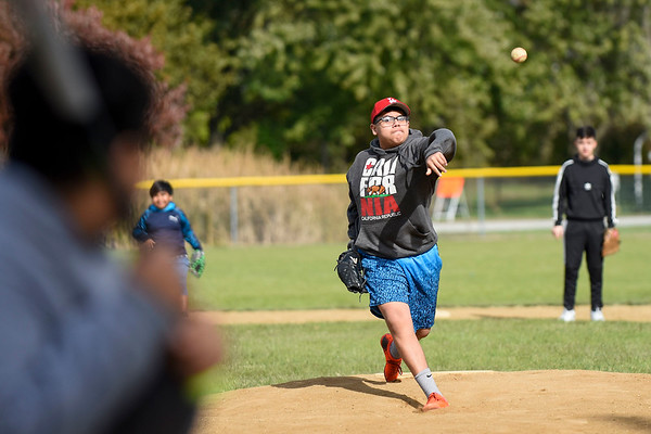 BEN MIKESELL | THE GOSHEN NEWS<br /> Goshen High School freshman Jesus Briano delivers a pitch to freshman Alexander Esparza Thursday afternoon at the Rogers Park baseball diamond in Goshen. Briano and his friends have been coming to the field all week to play baseball during fall break, he said. GHS students return to school Monday.