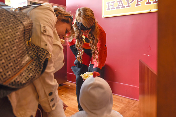 BEN MIKESELL | THE GOSHEN NEWS<br /> Kate Leaman with Shirley's Gourmet Popcorn hands a bag of popcorn to Titus Smith, 2, while trick-or-treating in downtown Goshen Wednesday.