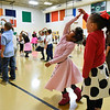 BEN MIKESELL | THE GOSHEN NEWS<br /> Concord West Side Elementary first-grader Iliana Vera Santos, left, spins around with the help of her classmate, Azelia Parks, right, during the 1950s sock hop to celebrate the 50th day of school Monday in West Side's gym. Music teacher Christa Jones led the first-grade students through many 50s era dances, including the twist, mashed potato and barrel roll.