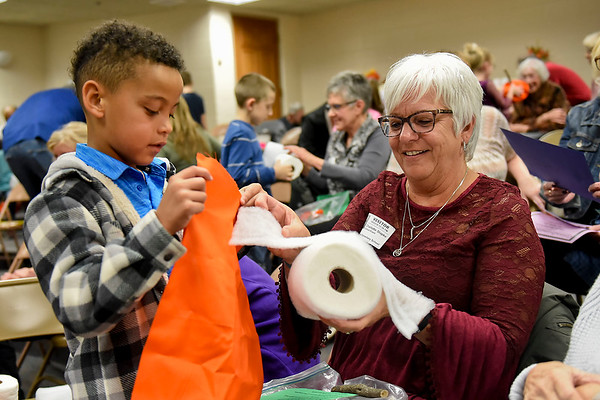 BEN MIKESELL | THE GOSHEN NEWS<br /> Eric Riddle, first-grader at Wakarusa Elementary School, makes a pumpkin craft with his grandmother Char Stapke, of South Bend, during Grandparent's Day Tuesday afternoon in Wakarusa.