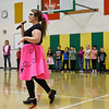BEN MIKESELL | THE GOSHEN NEWS<br /> Music teacher Christa Jones, donning her poodle skirt, gives directions prior to the sock hop Monday at Concord West Side Elementary.