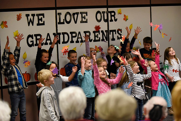 BEN MIKESELL | THE GOSHEN NEWS<br /> First-graders in Jeanne Balogh's class throw leaves into the air after finishing a song for Grandparent's Day Tuesday at Wakarusa Elementary School.