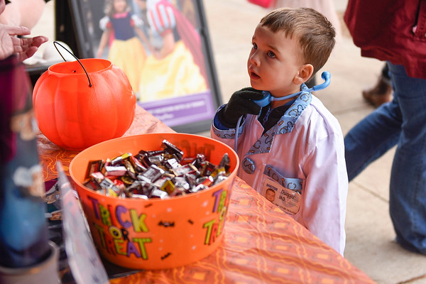 BEN MIKESELL | THE GOSHEN NEWS<br /> Wesley Dugger, 3, of Goshen, picks out his candy while trick-or-treating in downtown Goshen Wednesday.