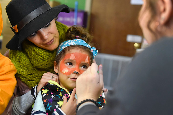 BEN MIKESELL | THE GOSHEN NEWS<br /> Ana Sofia Barahona, 3, sits with her mother Elisabeth, of Goshen, while getting her face painted as a fox during the Kids Fall Fest Wednesday at the Maple City Market. The Kids Fall Fest occurs every year while students are on their fall break.