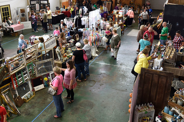 BEN MIKESELL | THE GOSHEN NEWS<br /> People tour various craft booths lined up for the 4th annual Harvest Festival Saturday morning in the downstairs section of the Old Bag Factory.