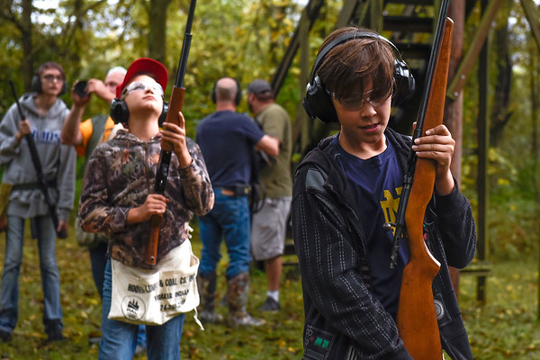 BEN MIKESELL | THE GOSHEN NEWS<br /> Eli Lehman, 11, right, and his brother Micah, 12, left, of Millersburg walk with their rifles to a shooting station during a youth skeet shooting event Saturday morning at the Nappanee Conservation Club.