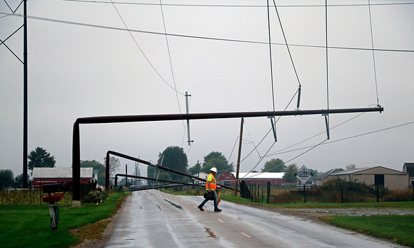 GEOFF LESAR | THE GOSHEN NEWS<br /> <br /> A Northern Indiana Public Service Company employee crosses 600 South in Millersburg Saturday evening. The road is temporarily closed after about 10 utility poles were downed likely due to winds Saturday morning.