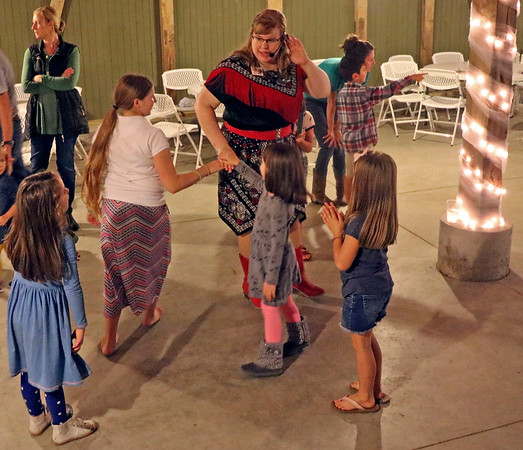 GEOFF LESAR | THE GOSHEN NEWS<br /> <br /> Teresa Berger, center, of South Bend, leads children in line dancing Sunday evening during the second annual Hoedown for Hope at the J. Weaver Barn in Goshen. Sponsored by Hope Mommies, a nonprofit supporting mothers and families who have experienced infant loss, the event drew more than 150 people, said Jessica Barnes, a care team coordinator with the organization. Barnes said the group's goal was to raise $8,000 through the event's silent auction with more than 70 items, bake sale and barbecue picnic, adding a total wouldn't be known until after the event's completion.