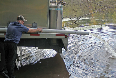 Roger Schneider | The Goshen News Terry Lauffer of Gollon Bait & Fish, Dodgeville, Wisconsin, relases a stream of young walleye into the Elkhart River Tuesday.