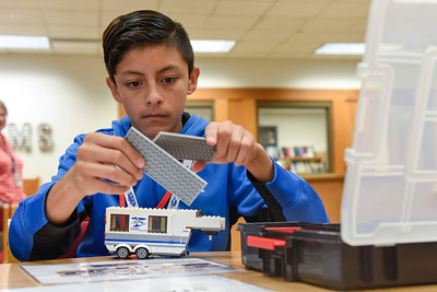 BEN MIKESELL | THE GOSHEN NEWS Jonathan Beatriz-Mares, eighth-grader at Goshen Middle School, works on the finishing touches on an RV during a LEGO exercise Tuesday morning in the school's media center. Beatriz-Mares worked with his classmates in assembly-line fashion to simulate how RVs are made.