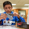 BEN MIKESELL | THE GOSHEN NEWS<br /> Jonathan Beatriz-Mares, eighth-grader at Goshen Middle School, works on the finishing touches on an RV during a LEGO exercise Tuesday morning in the school's media center. Beatriz-Mares worked with his classmates in assembly-line fashion to simulate how RVs are made.