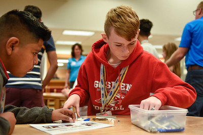 BEN MIKESELL | THE GOSHEN NEWS Preston Heeter, eighth-grader at Goshen Middle School, digs through a box of LEGO pieces during an exercise Tuesday morning with Thor Industries in the school's media center.